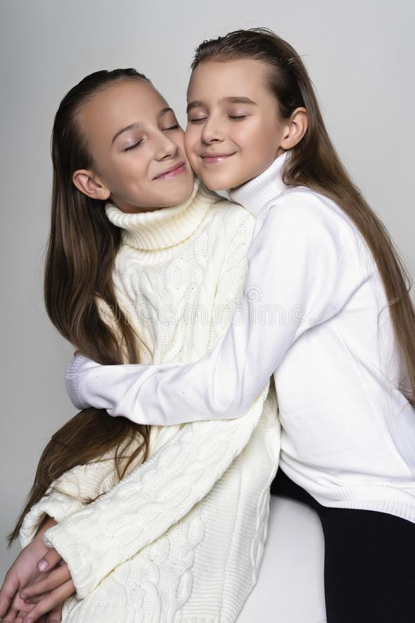 Two cute teenage girlfriends schoolgirls wearing white turtleneck sweaters, smiling sit, hugging each other in a friendly way. royalty free stock image