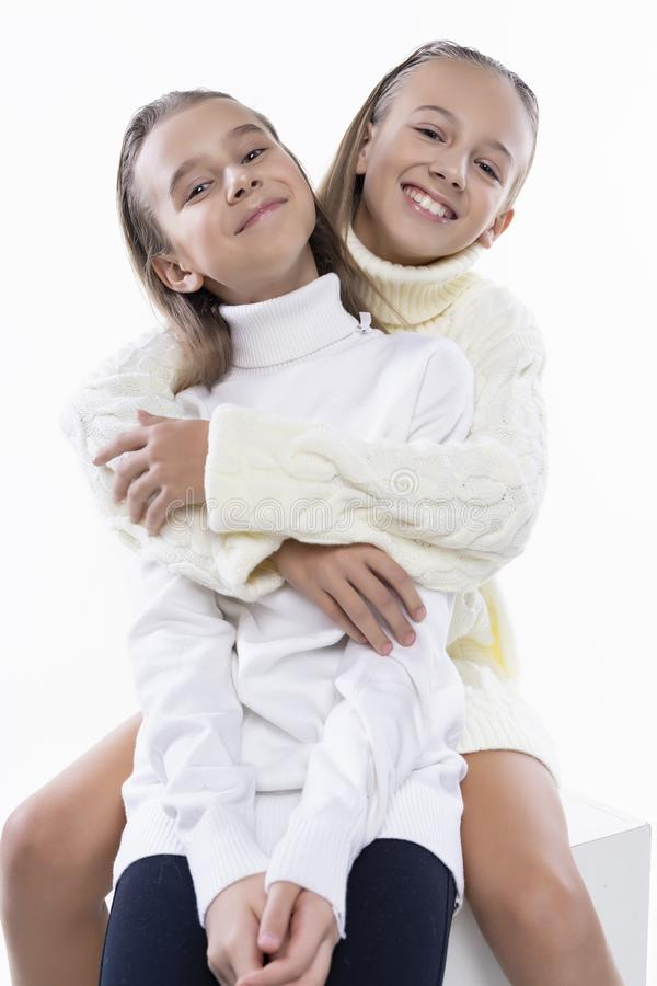 Two cute teenage girlfriends schoolgirls wearing white turtleneck sweaters, smiling sit, hugging each other in a friendly way. On white. Fashion and stock photography