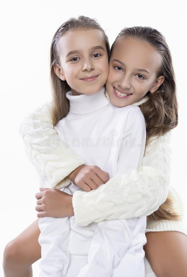 Two cute teenage girlfriends schoolgirls wearing white turtleneck sweaters, smiling sit, hugging each other in a friendly way. royalty free stock images