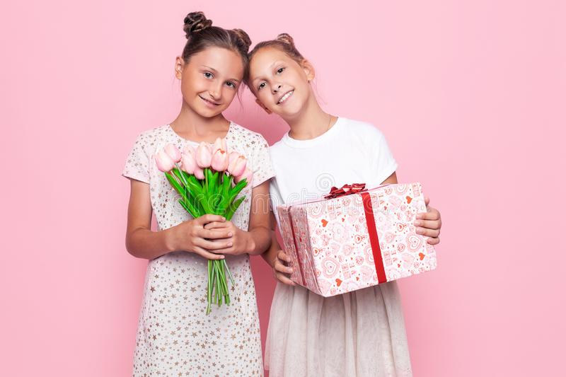 Two cute teenage girls in gentle dresses with a gift and a bouquet of flowers in their hands give gifts stock photos