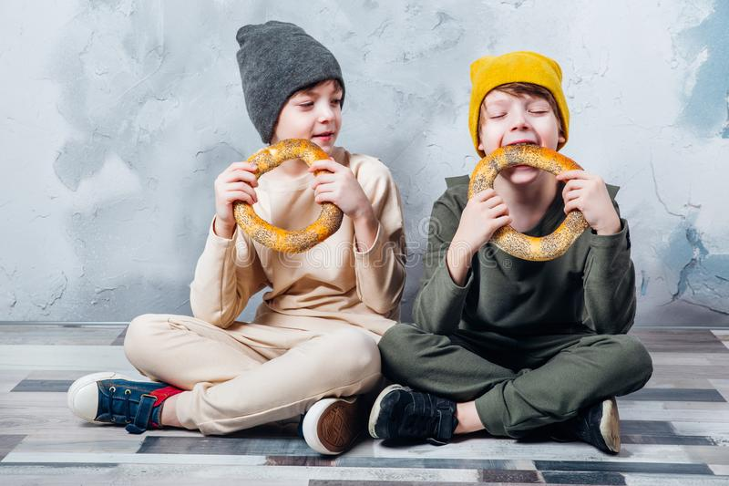 Two cute twin boys sitting on floor and happily eating bagel royalty free stock photo