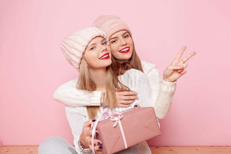 Two cute woman with red lips and hats giving gifts for a holiday and making peace by fingers. Concept Christmas and New. Two cute women with red lips and hats royalty free stock photography