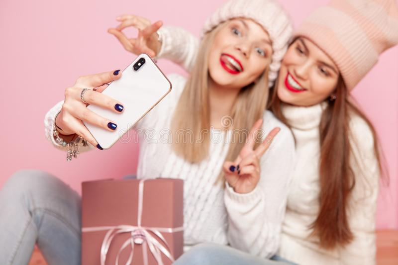 Two cute woman with red lips and hats sharing gift between themselves. Making selfie by smartphone. Concept Christmas stock photos