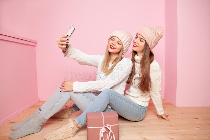 Two cute woman with red lips and hats sharing gift between themselves. Making selfie by smartphone. Concept Christmas royalty free stock photos