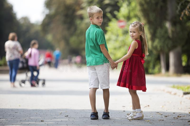 Two cute young blond smiling children, girl and boy, brother and sister holding hands on blurred bright sunny summer park alley stock images