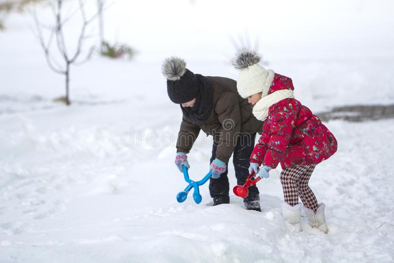 Two cute young children in warm clothing with bright snow clips playing having fun making snowballs on winter cold day on white br royalty free stock image