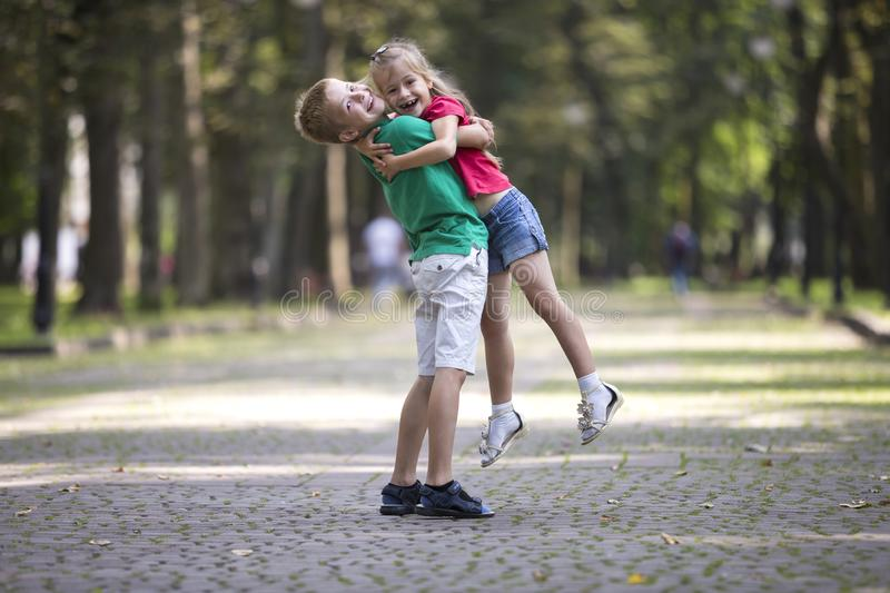 Two cute young funny smiling children, girl and boy, brother holding sister in his arms, having fun on blurred bright sunny park stock photography