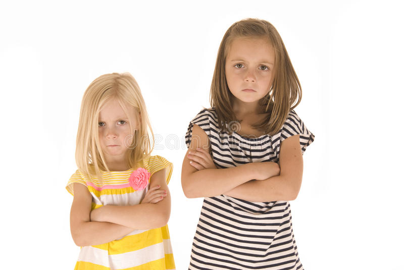 Two cute young girls mad and pouting stock images
