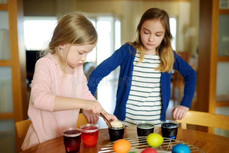 Two cute young sisters dyeing Easter eggs at home. Children painting colorful eggs for Easter hunt. Kids getting ready for Easter. Celebration. Family royalty free stock photography