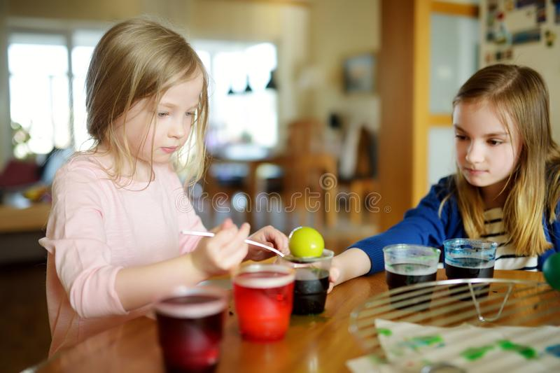 Two cute young sisters dyeing Easter eggs at home. Children painting colorful eggs for Easter hunt. Kids getting ready for Easter. Celebration. Family royalty free stock images