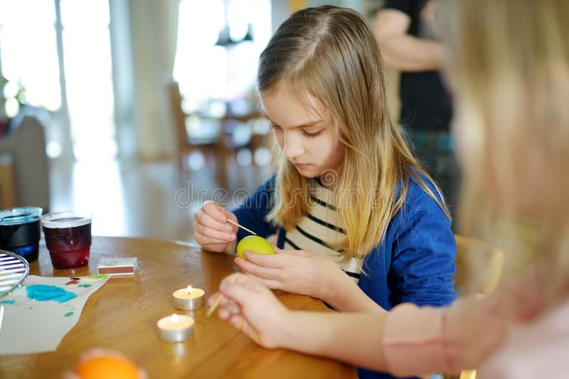Two cute young sisters dyeing Easter eggs at home. Children painting colorful eggs for Easter hunt. Kids getting ready for Easter. Celebration. Family stock photo