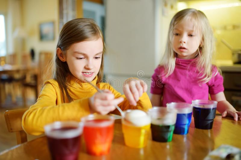 Two cute young sisters dyeing Easter eggs at home. Children painting colorful eggs for Easter hunt. Kids getting ready for Easter. Celebration. Family stock images
