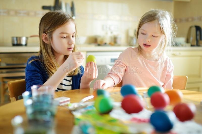 Two cute young sisters dyeing Easter eggs at home. Children painting colorful eggs for Easter hunt. Kids getting ready for Easter. Celebration. Family royalty free stock photos