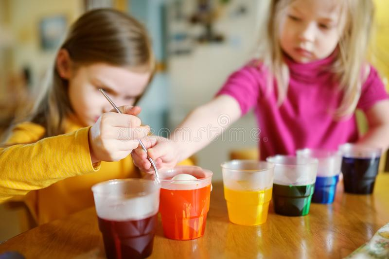 Two cute young sisters dyeing Easter eggs at home. Children painting colorful eggs for Easter hunt. Kids getting ready for Easter. Celebration. Family royalty free stock photo