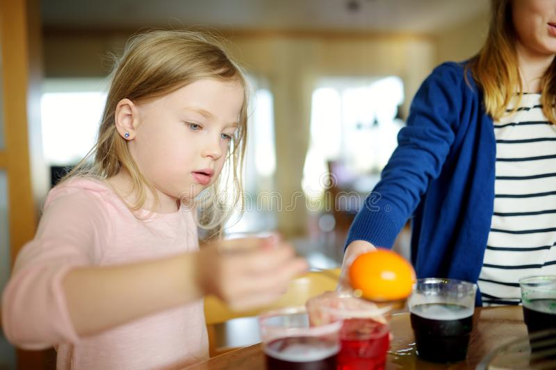 Two cute young sisters dyeing Easter eggs at home. Children painting colorful eggs for Easter hunt. Kids getting ready for Easter. Celebration. Family royalty free stock image
