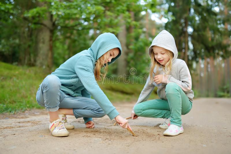 Two cute young sisters having fun during forest hike on beautiful summer day. Active family leisure with kids. Two cute young sisters having fun during forest stock photos