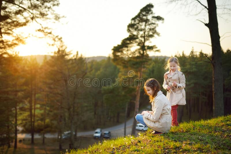 Two cute young sisters having fun together on beautiful spring day. Active family leisure with kids. Family fun outdoors stock photo