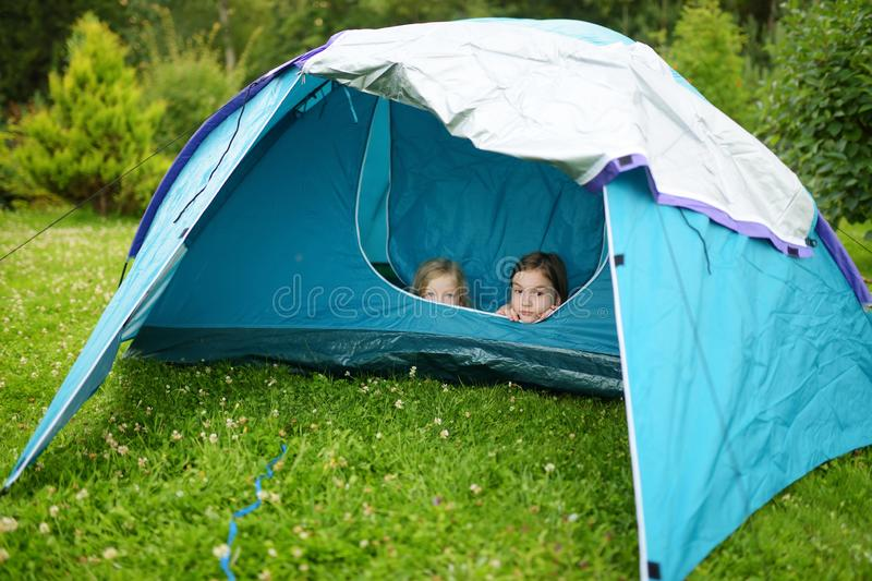 Two cute young sisters playing in a tent on a campsite. Active lifestyle, family recreational weekend, summer outdoor royalty free stock photos
