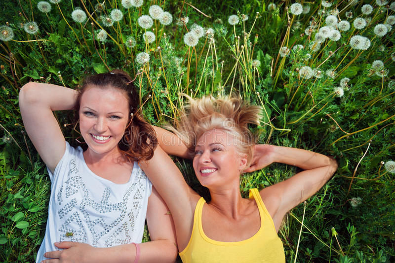 Two cute young women lying in the grass on summer sunny day outdoor. Happy girls enjoy nature. royalty free stock image