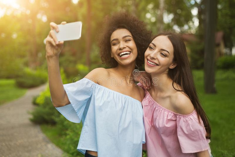 Two cute young women taking selfie in park royalty free stock images