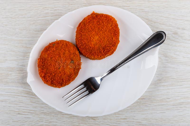 Two cutlets in breading, fork in dish on table. Top view. Two cutlets in breading, fork in white dish on wooden table. Top view stock photos