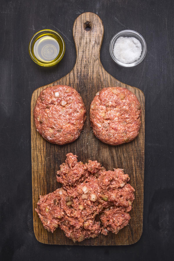 Two cutlets for burgers with minced meat on a cutting board with herbs, butter and salt wooden rustic background top view close stock photography