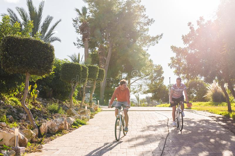 Two cyclists with bicycles at sunset in park.  stock photography