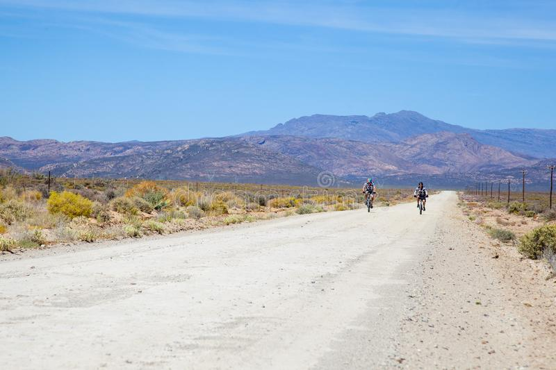 Two cyclists riding on a dirt road in the Karoo. On a very dry and hot day. Great scenic riding and adventure can be found in the Karoo. Breede River D.C, South stock images