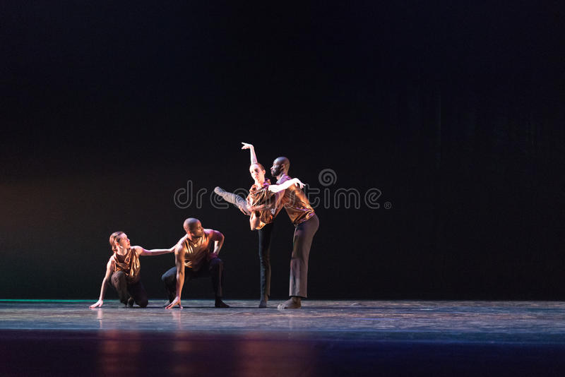 Two 2 dancers pose against dark blue background on stage stock image