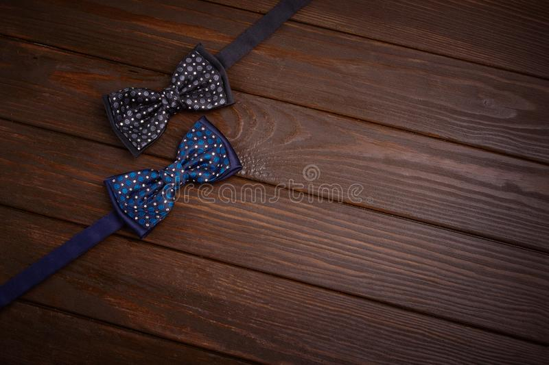 Two dark bowties with polka dots on a dark brown wooden board background. royalty free stock image