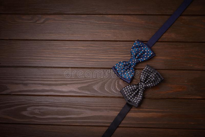 Two dark bowties with polka dots on a dark brown wooden board background. stock images