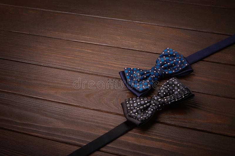 Two dark bowties with polka dots on a dark brown wooden board background. royalty free stock images