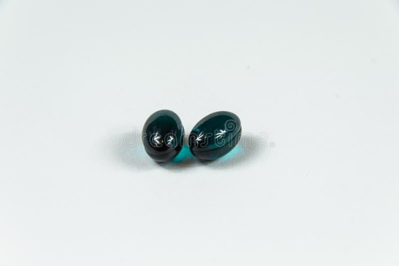 Two dark green soft gelatine capsules. Two dark green soft gelatine capsules in bright light stock image