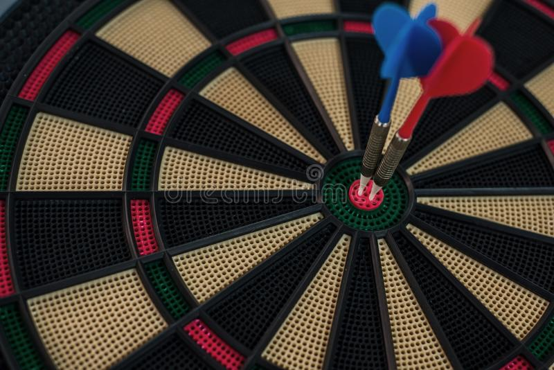 Two darts on a dart board. Two darts on a dartboard`s center stock photo