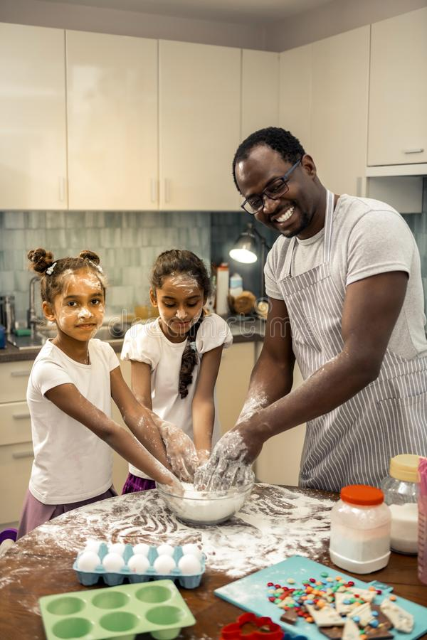 Two daughters feeling excited while cooking cupcakes with father. Cupcakes with father. Two daughters feeling excited kneading dough while cooking cupcakes with stock photography