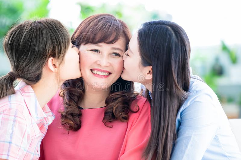 Two daughters kiss mom at home royalty free stock photo