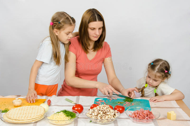 Two daughters are watching with interest as mother chopped green stock photos