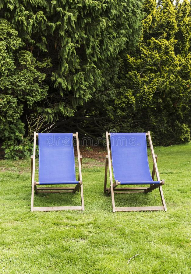 Two deck chairs in a garden with solid trees as a background. Two deck or leisure chairs on grass with a background of solid trees giving copy space royalty free stock photography