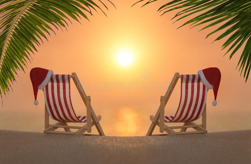 Two deckchairs with red Christmas Santa hats at ocean sandy palm sunset beach. Two striped deckchairs with red Santa hats for romantic couple at ocean sandy royalty free stock photo