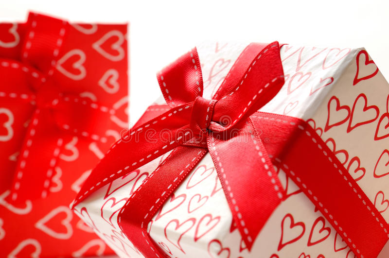 Two decorative gift boxes with hearts printed isolated close up. Two decorative gift boxes with red ribbon and hearts printed close up. Front view. White stock image
