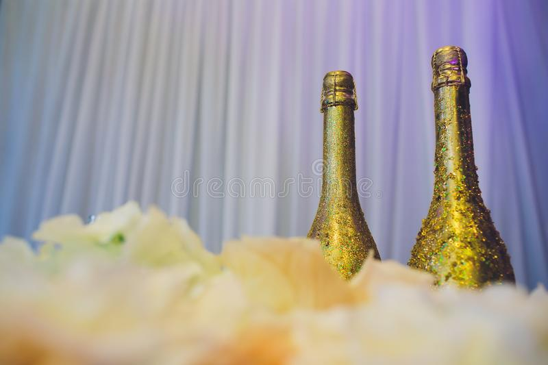 Two decorative gold bottles of luxury champagne with copyspace for your New Year, Christmas or wedding greeting or royalty free stock photography