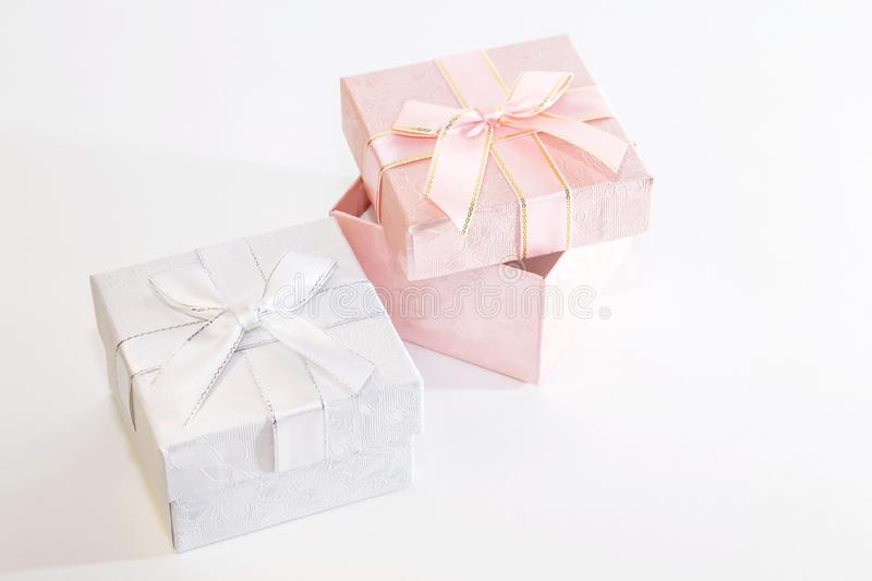 Two decorative holiday gift boxes with ribbon bow for congratulations, surprise, presentation in white and pink on a white royalty free stock images