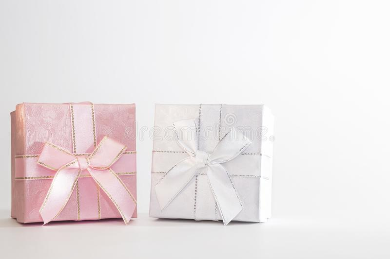 Two decorative holiday gift boxes with ribbon bow for congratulations, surprise, white and pink presentations on a white stock photo