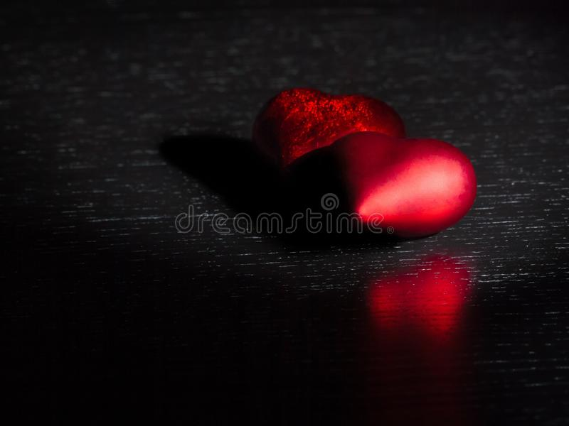 Two decorative red hearts on black dark light and on wood table, concept of valentine day stock photography