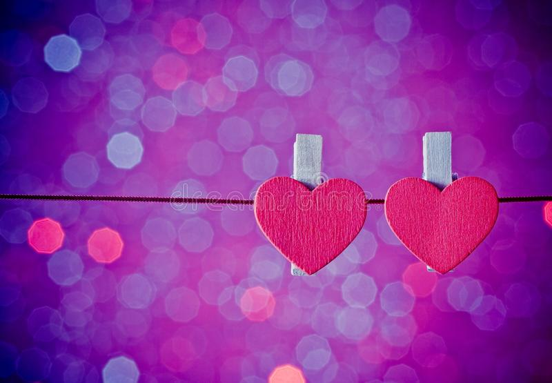 Two decorative red hearts hanging against blue and violet light bokeh background, concept of valentine day stock photo