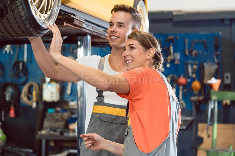 Two dedicated auto mechanics smiling while checking the wheels of a tuned car royalty free stock images