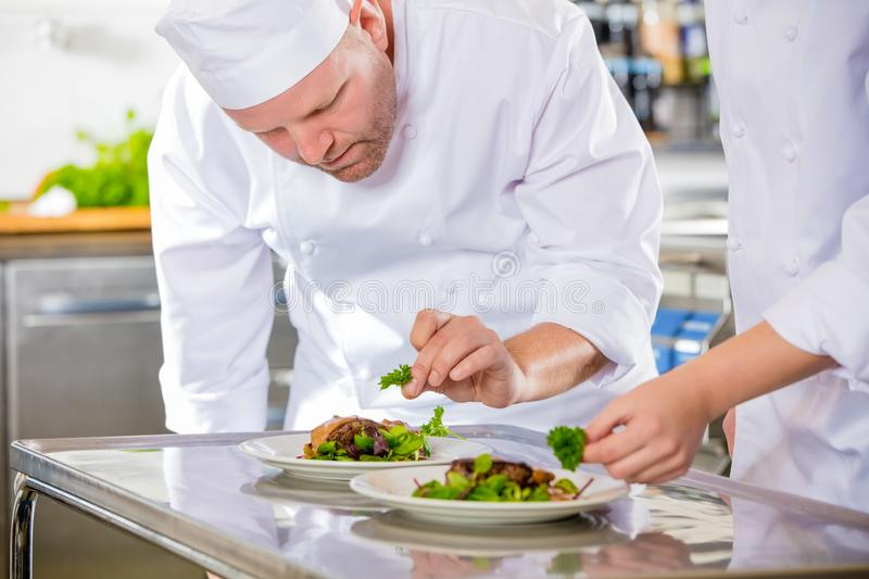 Two dedicated chefs prepares steak dish at gourmet restaurant stock images