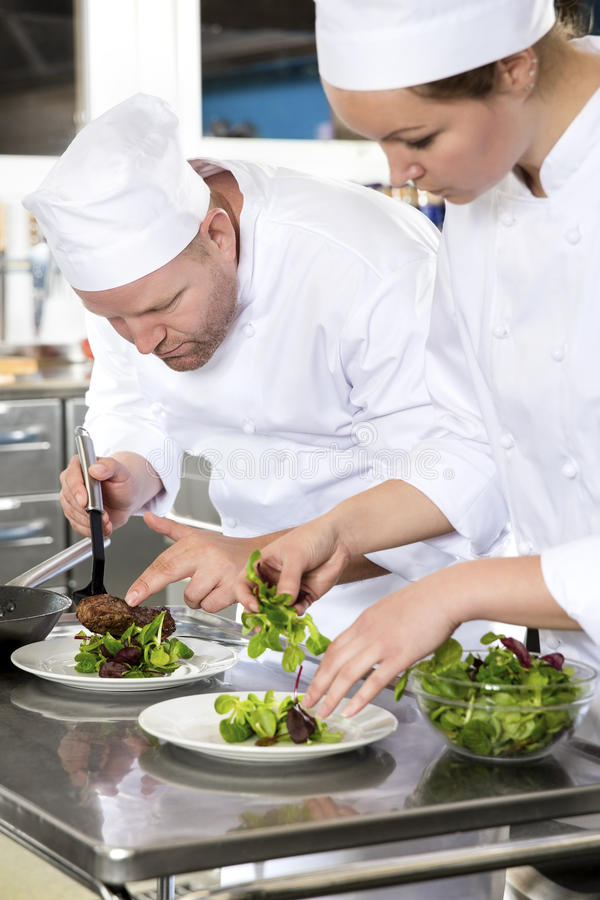 Two dedicated chefs prepares steak dish at gourmet restaurant. Professional and dedicated chefs prepares beef meat dish in a professional kitchen at gourmet stock photos