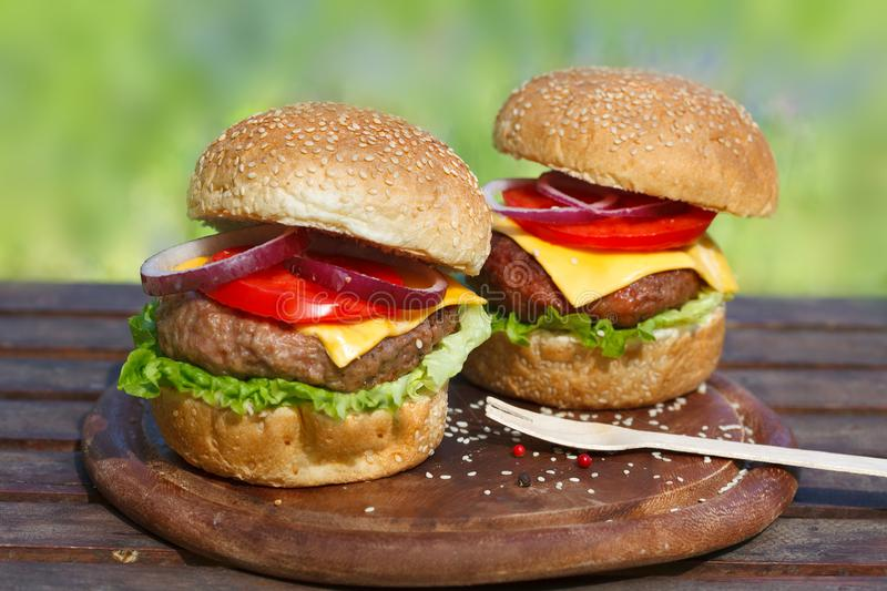 Two delicious burgers on wooden board. Fresh, tasty hamburgers. Soul food stock photography