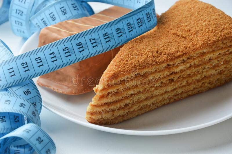 Two delicious cream cakes on a white plate. delicious sweets. blue ribbon meter. the waist measurement. diet, weight loss. Two delicious cream cakes on a white stock image